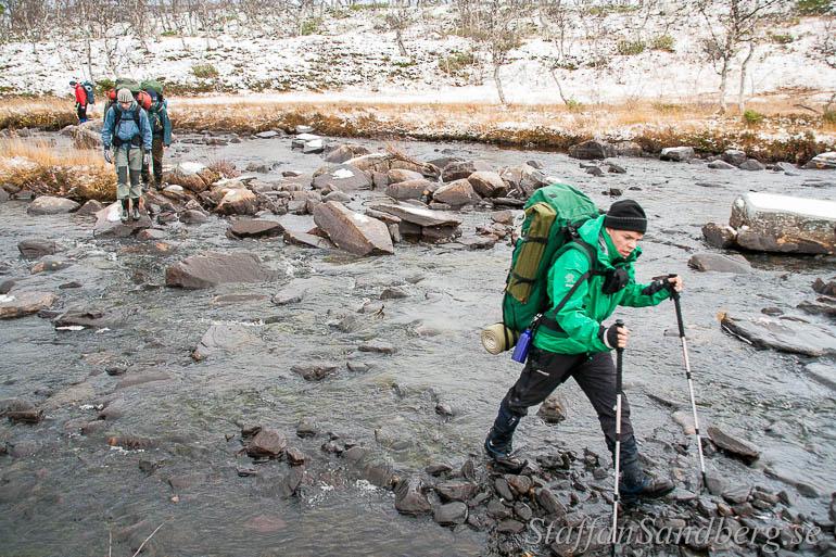 En grupp går över en bäck med vandringskängor.