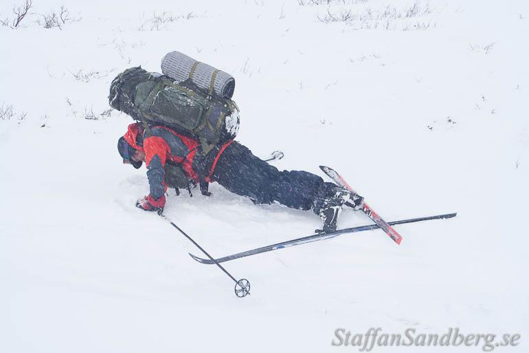 Skidåkare ligger på marken med ryggsäck