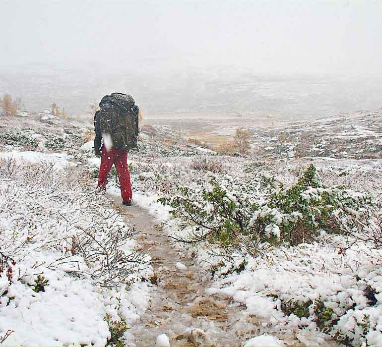 Vandring i snöblandat regn med ryggsäck